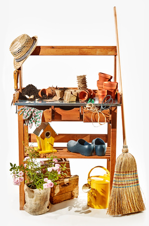 Wooden shelves with gardening accessories , nesting box, tools, flowerpots and a garden broom over white in a concept of the spring season