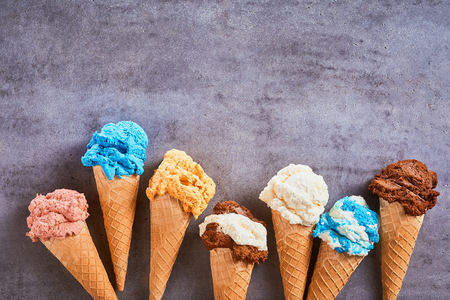 Border of assorted flavours of gourmet artisanal ice cream served in sugar cones over textures grey slate with copy space Stockfoto