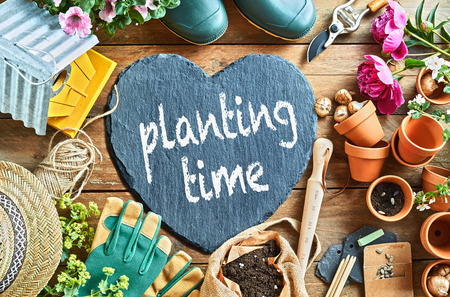 Planting time concept with garden equipment, tools, gloves and pots for flowers, with heart-shaped blackboard and chalk sign, viewed from above in full frame Imagens