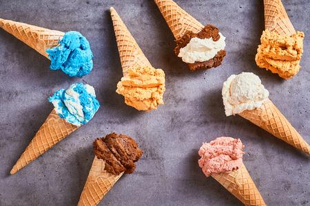 Coni di gelato deliziosi specialità con una varietà di sapori diversi disposti come una natura morta su uno sfondo grigio ardesia