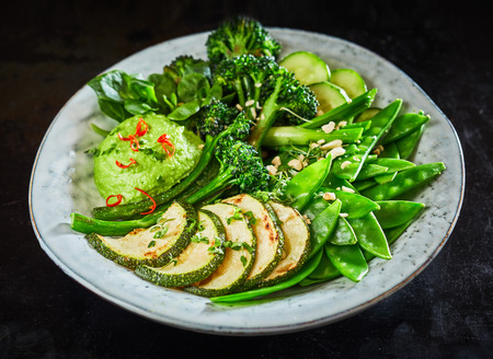 Tasty green vegetable Buddha bowl with beans, broccoli, zucchini and avocado dip