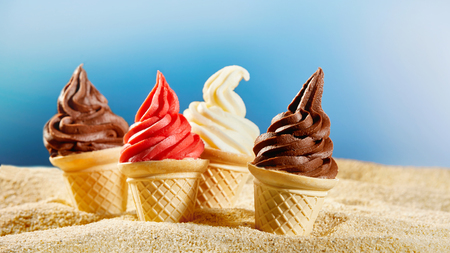 Colourful ice cream in crunchy cones stuck into sand Stock Photo