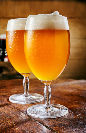 Two glasses of cold fresh beer in close up standing on wooden table Stock Photo