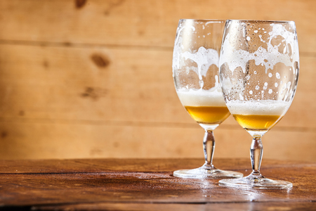 Two emptied glasses of beer on a counter with remnants of the lager and froth in the glass and copy space on a wooden background