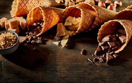 Close up view of wafer cones filled with chocolate, coffee and other ingredients
