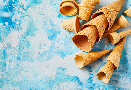 Empty crispy wafer cones against blue white background