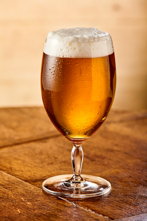 Chilled beer with a frothy head in a tall stemmed glass standing on an old rustic wooden table in a close up view Stock Photo