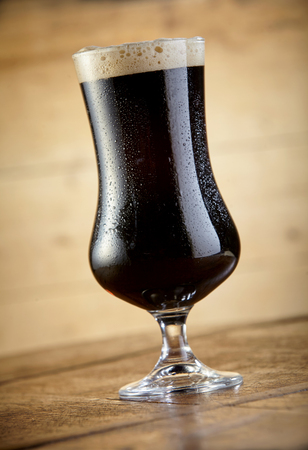 Close up view of cold fresh beer goblet standing on table against wooden background Stockfoto