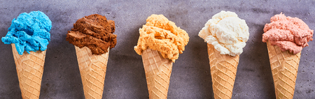 Panorama banner with assorted different flavors of artisanal ice-cream served in sugar cones in a row on a slate background Stock Photo