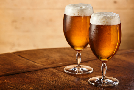 Two tall stemmed glasses of fresh chilled draft or craft beer with fresh frothy heads standing side by side on an old table with lateral copy space