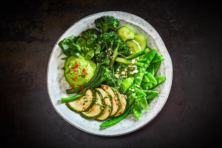 High angle view of green vegetable Buddha bowl with avocado dip