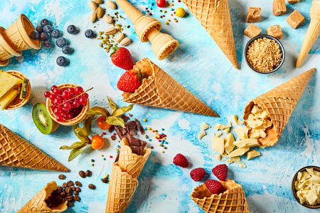 Crispy wafer cones filled with fruits and sweet ingredients against blue background
