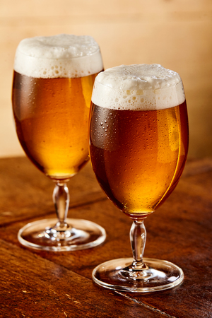 Two glasses of delicious ice cold craft beer or lager with fresh frothy head standing on an old wooden table or counter