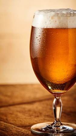 Glass of cold beer with frothy head in a cropped close up side view on a wooden table Stock Photo