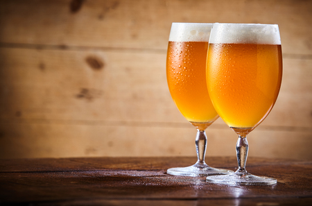 Two chalices of fresh cold pale beer standing on table against wooden background
