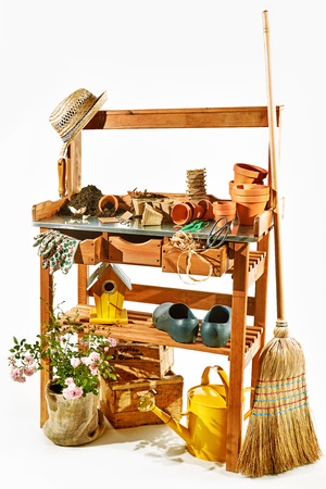 Wooden shelves with gardening tools against white background