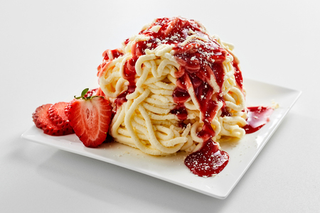 Plate with spaghetti ice cream dessert with sweet strawberry topping