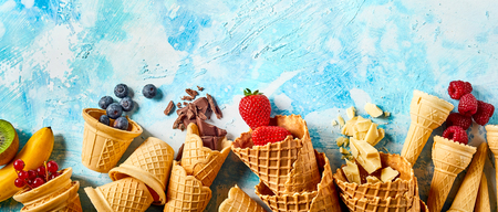 Crunchy wafer cones filled with fruits against blue background Foto de archivo - 99177145