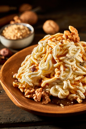 Spaghetti ice cream dessert with walnut topping in close up view