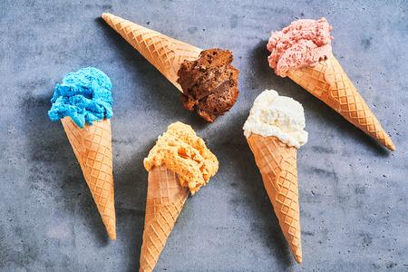 Cinque gusti assortiti di gelato estivo gourmet serviti in coni di zucchero sparsi su uno sfondo grigio ardesia Archivio Fotografico