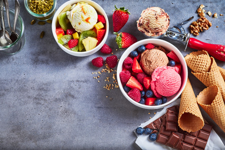 Tubs of fresh fruit with ice cream and ingredients including, chocolate, berries, walnuts, pistachio and a metal scoop for serving on slate with copy space, top down view Banco de Imagens - 99177150
