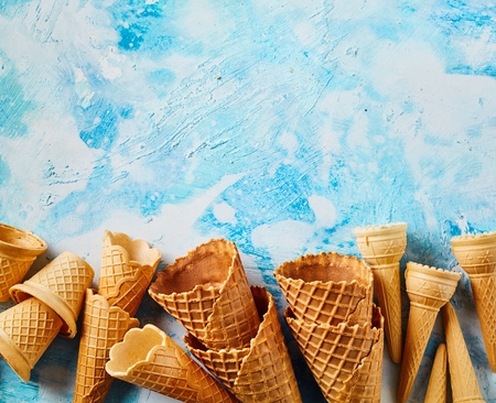 Crunchy empty wafer cones against blue background Imagens