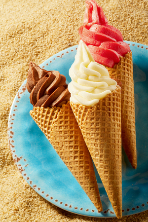 Ice cream in crunchy wafer cones on blue plate against sandy beach