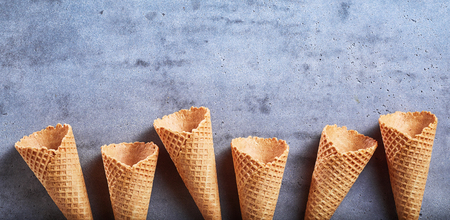 Border of empty ice cream wafer sugar cones on a textured grey slate background with copy space in panorama banner format