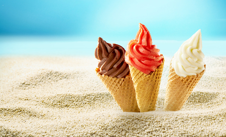 Three ice cream cones stuck into beach white sand, viewed against sea shore and blue sky in close-up with copy space Stock Photo
