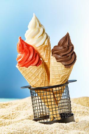 Three crispy cones with ice cream stuck in container on sandy beach