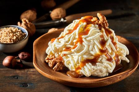 Spaghetti ice cream dessert with walnut sauce on wooden table Zdjęcie Seryjne