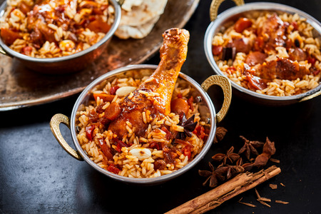 Individual servings of spicy Arabian kabsa with long grained rice, vegetables and meat with dried star anise and cinnamon ingredients alongside Stockfoto