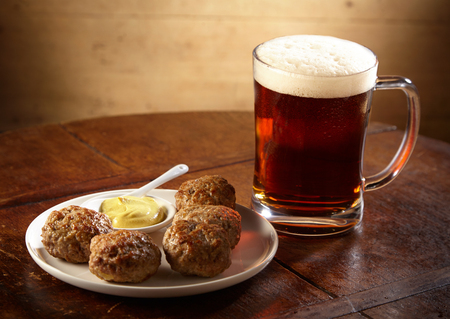 Plate of spicy meatballs served with a glass tankard or mug of chilled beer with a frothy head and copy space