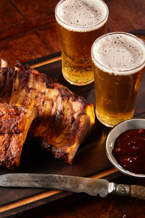 Delicious spicy spare ribs served with chilled beers, a dipping sauce and sharp knife in a pub or tavern
