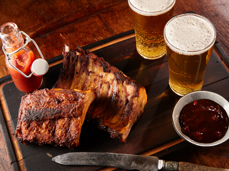 Two portions of spicy grilled spare ribs served with cold beers and a knife on a tray in a tavern or pub
