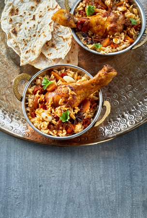 Bowls of spicy Arabian kabsa with meat and vegetables in long grain aromatic Basmati rice served with Naan bread on a silver metal tray with copy space in a top down view Stockfoto