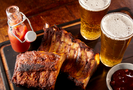 Two spicy barbecued ribs portions with chilled beer in tall glasses served with ketchup and chutney in a pub or tavern for a finger lunch