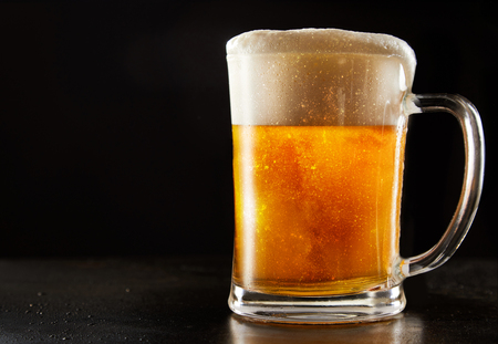 Large glass mug of effervescent chilled glitter draft beer with a good frothy head over a reflective black background with copy space Standard-Bild