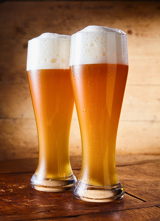 Two tall elegant pint glasses of cold wheat beer with a frothy head on a wooden bar table conceptual of Oktoberfest