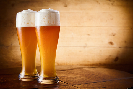 Two ice cold glasses of frothy larger or wheat draft beer on a rustic bar counter with side vignette and copy space