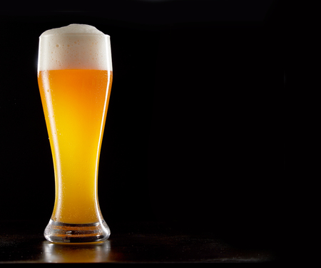 Single tall stylish glass of chilled frothy wheat beer on a reflective black background with copy space Stock Photo