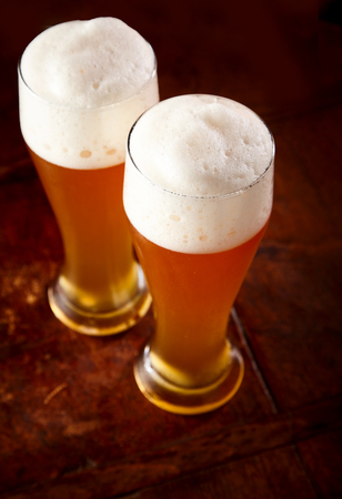 Two tall glasses of wheat beer with good frothy heads viewed high angle with focus to the froth on a wooden bar counter or table Stock Photo