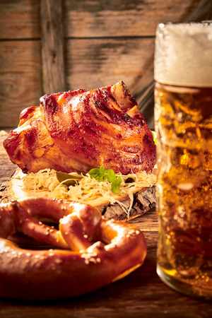 Roast pork knuckle on a bed of sauerkraut served with a cold frothy beer and pretzel in a rustic tavern at Oktoberfest