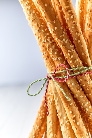 Closeup of savory sesame seed grissini breadsticks tied with string in the Italian national colors of red, white and green Banco de Imagens