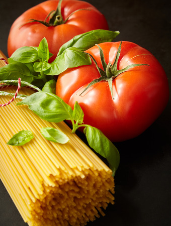 Bunch of raw spaghetti among tomato with fresh basil in close up