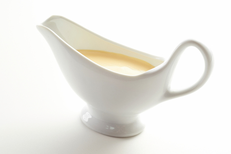 Sauce boat filled with gourmet Hollandaise sauce made from whisked egg yolk, lemon juice, melted butter and seasoning over a white background