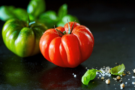 Fresh whole ripe red tomato with water droplets on a black surface with copy space and fresh basil, coarse salt and peppercorns