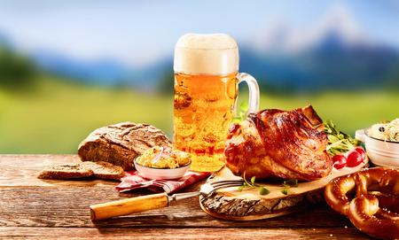 Traditionelle deutsche Küche, geröstetes Schinken-Sprunggelenk von Schweinshaxe, Brezel mit Obatzter-Käse-Aufstrich und ein Glas helles Bier auf Holztisch Standard-Bild