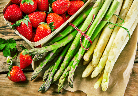Bundles of fresh white and green spring asparagus with a punnet of ripe red juicy strawberries on a wooden table in a close up view