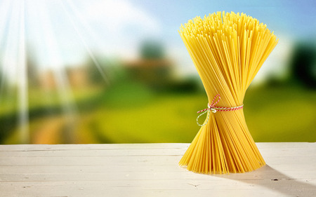 Twisted bundle of dried Italian spaghetti standing upright outdoors on a garden table in summer sunshine with copy space